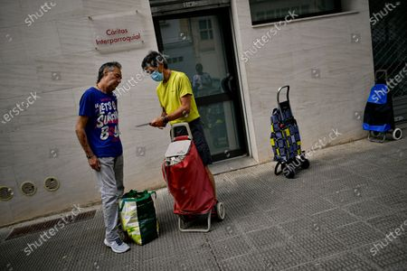 Luis Miguel Beaumont, 57 years old unemployed, left, talks with Kiko, staff worker of charity foundation Caritas, after he received a pack of foods from charity foundation Caritas, to last the next two weeks, in Estella, around 38 kms (23, 61 miles) from Pamplona, northern Spain, . Spain is beginning to suffer an economic crisis due to the coronavirus pandemic