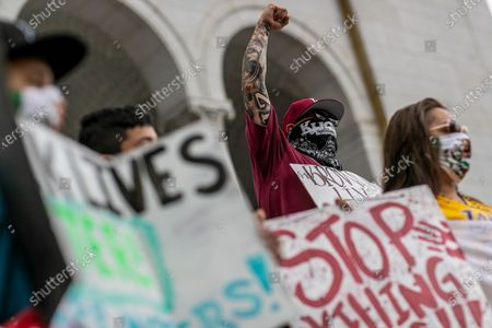 Los Angeles, CA, Sunday, June 28,2020 - Stephan Ruelas raises his fist while joining hundreds of low riders and supporters outside City Hall to protest police brutality and systemic racism. (Robert Gauthier / Los Angeles Times)