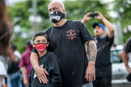 Los Angeles, CA, Sunday, June 28,2020 -Gerardo Gomez with his son Jayden, join hundreds of low riders outside City Hall protesting police brutality and systemic racism. (Robert Gauthier / Los Angeles Times)