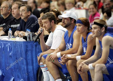 """Justin Timberlake--flanked by fellow NSYNCer Joey Fatone, Shannon Elizabeth, and David Gallagher from the hit tv show """"7th Heaven""""-- watches from the bench and takes the mike to call the action, after having demonstrated his mean basketball skills, at the Challenge For The Children All-Star Celebrity Basketball Game--in which """"The Knights"""" and """"The Daze"""", two teams of singers, actors, and athletes vie for bragging rights--part of the 7th Annual Challenge For The Children weekend in which NSYNC and celebrity friends have taken over the """"Windy City"""", Chicago, Illinois, for a series of events to raise funds and awareness for various children's charities; at the Allstate Arena in Chicago, Ill."""