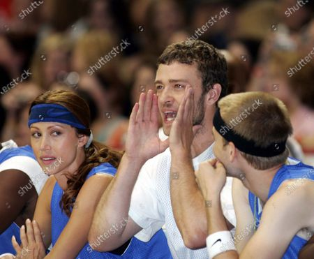 """Justin Timberlake--flanked by Shannon Elizabeth, and David Gallagher from the hit tv show """"7th Heaven""""-- watches from the bench after having demonstrated his mean basketball skills, at the Challenge For The Children All-Star Celebrity Basketball Game--in which """"The Knights"""" and """"The Daze"""", two teams of singers, actors, and athletes vie for bragging rights--part of the 7th Annual Challenge For The Children weekend in which NSYNC and celebrity friends have taken over the """"Windy City"""", Chicago, Illinois, for a series of events to raise funds and awareness for various children's charities; at the Allstate Arena in Chicago, Ill."""
