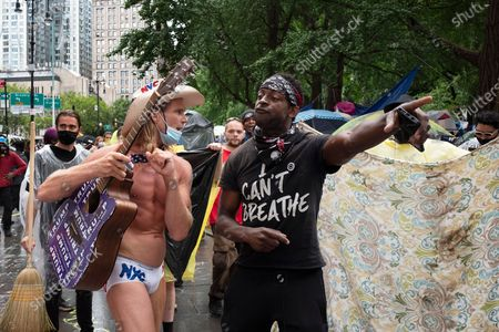 Robert Burck, left, also known as the Naked Cowboy, is forced from an encampment of protesters at City Hall, in New York. Burck is a pronounced supporter of President Donald Trump. New York City lawmakers approved an austere budget early Wednesday that will shift $1 billion from policing to education and social services in the coming year, acknowledging protesters' demands to cut police spending but falling short of what activists sought