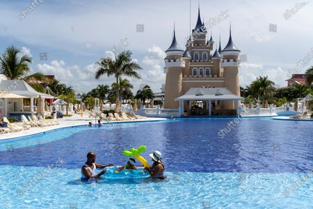 People enjoy a pool in the Bahia Principe Fantasia resort in Punta Cana, Dominican Republic, on 01 July 2020, after the Dominican authorities issued the protocol of tourist activities that will come into force today, with the reopening of the hotels, which among other the measures leave adults the option of putting on masks on the beaches and discourages them for children. The reopening in the middle of the coronavirus pandemic, which goes hand in hand with the restart of international flights to and from the country, limits occupancy in hotels with more than 500 rooms to 30% during July, increasing it to 50% in August and 75% in December.
