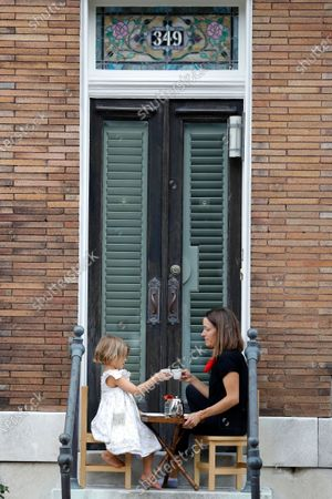 Rosie Wood, left, 5, cheers with her mother, Katie Wood, as they enjoy an early afternoon tea time on their steps, in the Federal Hill neighborhood of Baltimore