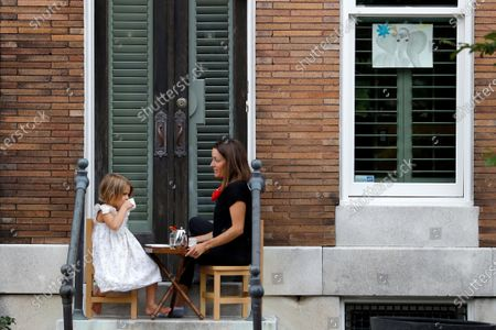 Rosie Wood, left, 5, sips while sitting with her mother, Katie Wood, during an early afternoon tea time on their steps, in the Federal Hill neighborhood of Baltimore