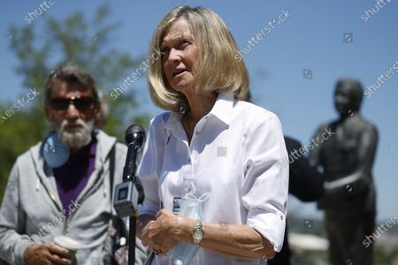 Janet Johnson of Pawcatuck, Ct., front, speaks at a news conference while her husband, Norman, looks on after the sentencing hearing, for James Curtis Clanton in the death of Helene Pruszynski, Janet Johnson's younger sister, four decades ago in Castle Rock, Colo. Clanton has been sentenced to life in prison