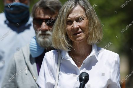 Janet Johnson of Pawcatuck, Ct., front and her husband, Norman, listen to speakers at a news conference, after the sentencing hearing for James Curtis Clanton in the death of Helene Pruszynski, Janet Johnson's younger sister, four decades ago in Castle Rock, Colo. Clanton was sentenced to life in prison