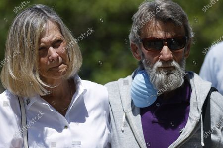 Janet Johnson of Pawcatuck, Ct., left, is hugged by her husband, Norman, as they listen to speakers at a news conference, after the sentencing hearing for James Curtis Clanton in the death of Helene Pruszynski, Janet Johnson's younger sister, four decades ago in Castle Rock, Colo. Clanton was sentenced to life in prison