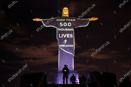 """The Christ the Redeemer statue is lit up with a message that reads in Portuguese; """"More than 500 thousand lives world"""" in reference to the people who have died from COVID-19 worldwide, in Rio de Janeiro, Brazil"""