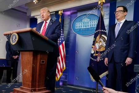 President Donald Trump speaks during a news briefing at the White House, in Washington, as Treasury Secretary Stephen Mnuchin looks on
