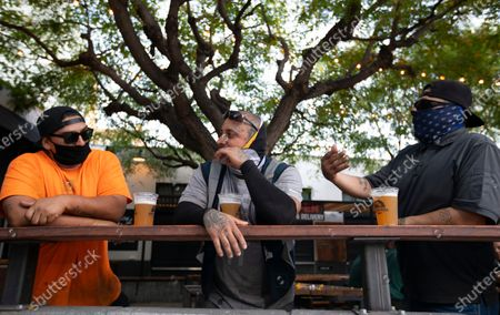 Stock Picture of Adan Gutierrez, left, Ramon Ayala, middle, and Vicente Fernandez, right, enjoy a beer outside the Central Market during the evening on Tuesday, June 30, 2020 in Los Angeles, CA. They were all wearing masks and keeping a distance for one another. Inside the brewery remains open because they also sell food. Citing the rapid pace of coronavirus spread in some parts of California, Gov. Gavin Newsom ordered seven counties including Los Angeles on Sunday to immediately close any bars and nightspots that are open and recommended eight other counties take action on their own to close those businesses. (Francine Orr / Los Angeles Times)