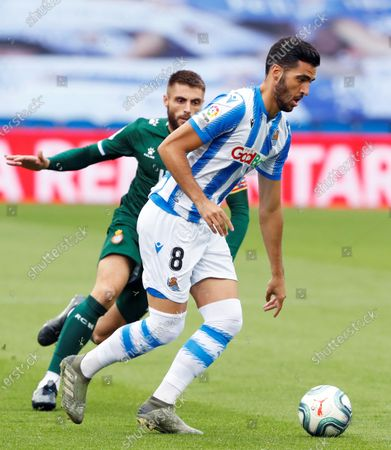 Real Sociedad's Mikel Merino (L) in action against Espanyol's David Lopez (R) during the Spanish La Liga soccer match between Real Sociedad and RCD Espanyol at Reale Arena stadium in San Sebastian, northern Spain, 02 July 2020.