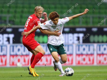 Yuya Osako (R) of Bremen in action against Sebastian Griesbeck (L) of Heidenheim during the German Bundesliga relegation playoff, first leg soccer match between Werder Bremen and FC Heidenheim in Bremen, Germany, 02 July 2020.