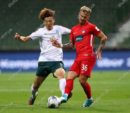 Yuya Osako (L) of Bremen in action against Niklas Dorsch (R) of Heidenheim during the German Bundesliga relegation playoff, first leg soccer match between Werder Bremen and FC Heidenheim in Bremen, Germany, 02 July 2020.