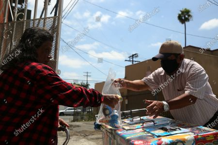 Angela Alfonso Santos, 71, purchases three paleta's from Mauro Rios Parra on Tuesday, June 16, 2020 in Los Angeles, CA. Parra came to the U.S. from Mexico about 20 years ago to financially support his wife and three kids in Oaxaca and he has been selling paletas ever since. (Dania Maxwell / Los Angeles Times)
