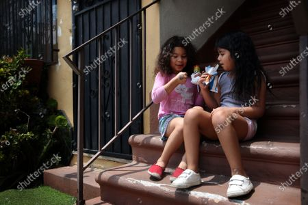 Elizabeth Sanchez, left, 5, and Mia Estrada, right 6, sit on steps in their apartment complex eating paleta's from Mauro Rios Parra on Tuesday, June 16, 2020 in Los Angeles, CA. Parra usually stops in this apartment complex on his route. (Dania Maxwell / Los Angeles Times)