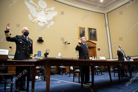 "Admiral Brett Giroir, United States Assistant Secretary for Health, left, Rear Admiral John P. Polowczyk, Vice Director, J4, Joint Staff, leader of the Supply Chain Stabilization Task Force and vice director of logistics of the Joint Chiefs of Staff, and Kevin Fahey, assistant Defense secretary for acquisition, swear in before testifying during a House Oversight and Reform Committee hearing on ""The Administration's Efforts to Procure, Stockpile, and Distribute Critical Supplies"" in the Capitol in Washington. (Pool photo by Caroline Brehman/CQ Roll Call)"