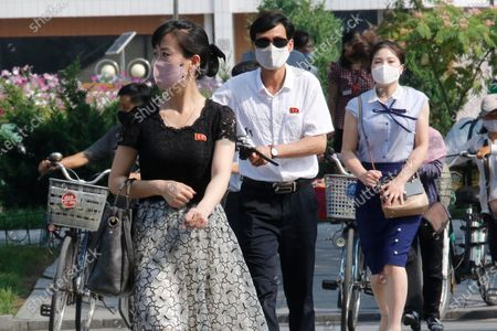 "People wearing masks walk in the Ryomyong street in Pyongyang, North Korea . North Korean leader Kim Jong Un urged officials to maintain alertness against the coronavirus, warning that complacency risked ""unimaginable and irretrievable crisis,"" state media said Friday"