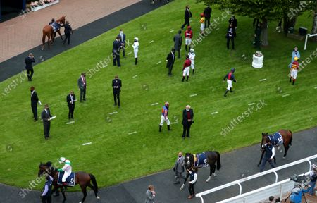 Jockeys and trainers social distancing in the parade ring ahead of the Investec Derby at Epsom Racecourse. PA Photo. Issue date: Saturday July 4, 2020. See PA story RACING Epsom. Photo credit should read: David Davies/PA Wire