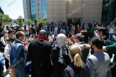 Hatice Cengiz, centre back to camera, the fiancee of slain Saudi journalist Jamal Kashoggi, talks to members of the media outside a court in Istanbul, where the trial in absentia of two former aides of Saudi Crown Prince Mohammed bin Salman and 18 other Saudi nationals over the 2018 killing of the Washington Post columnist had began. Turkish prosecutors have indicted the 20 Saudi nationals over Khashoggi's grisly killing at the Saudi Consulate in Istanbul that cast a cloud of suspicion over Prince Mohammed and are seeking life prison terms for defendants who have all left Turkey. Saudi Arabia rejected Turkish demands for the suspects' extradition and put them on trial in Riyadh