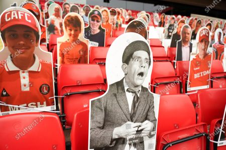 Norman Wisdom amongst cardboard cut outs of Charlton fans in the home end at The Valley