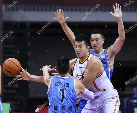 Stock Photo of Jeremy Lin (Front) and Zhai Xiaochuan (Rear) of Beijing Ducks vie with Zou Yuchen of Bayi Rockets during a match between Beijing Ducks and Bayi Rockets at the 2019-2020 Chinese Basketball Association (CBA) league in Qingdao, east China's Shandong Province, July 3, 2020.