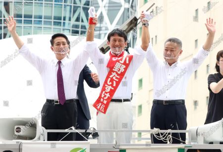 A candidate Taisuke Ono (C) raises hands with Japan Restoration Party Secretary General Nobuyuki Baba (R) and former Democratic Party leader Seiji Maehara (L) after they delivered campaign speeches for the Tokyo gubernatorial election in Tokyo on Friday, July 3, 2020. Tokyo gubernatorial election will be held on July 5.