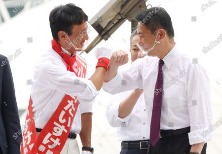 A candidate Taisuke Ono (L), former Kumamoto prefecture vice Governor bumps fists with former Democratic Party leader Seiji Maehara (R) as they deliver campaign speeches for the Tokyo gubernatorial election in Tokyo on Friday, July 3, 2020. Tokyo gubernatorial election will be held on July 5.
