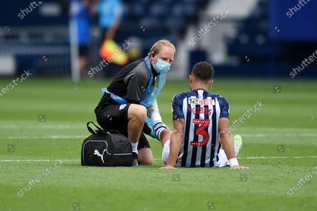 A member of the West Bromwich Albion medical team attends to Kieran Gibbs of West Bromwich Albion.