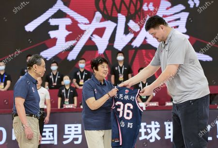 Chinese Basketball Association (CBA) president Yao Ming (R) presents a jersey to Li Shaofen (C), who is wife of Chinese renowned respiratory specialist Zhong Nanshan (L) and also a former Chinese National Women's Basketball team player, before a match between Jiangsu Dragons and Guangdong Southern Tigers at the 2019-2020 Chinese Basketball Association (CBA) league in Dongguan, south China's Guangdong Province, July 3, 2020.