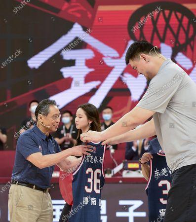 Chinese Basketball Association (CBA) president Yao Ming (R) presents a jersey to Chinese renowned respiratory specialist Zhong Nanshan (L) before a match between Jiangsu Dragons and Guangdong Southern Tigers at the 2019-2020 Chinese Basketball Association (CBA) league in Dongguan, south China's Guangdong Province, July 3, 2020.