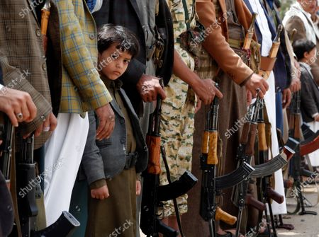 A child stands amongst armed Houthi supporters during a gathering to mobilize more fighters against Saudi-backed government forces, in Sana'a, Yemen, 03 July 2020. Yemen has been experiencing a power struggle since late 2014 between the Houthis and the Saudi-backed government, which sparked a full-blown armed conflict in March 2015 when the Saudi-led coalition launched an airstrike campaign against the Houthis.