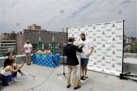 Competitive eating champion Joey Chestnut (C) on the scale at weigh-in for the Nathan's Famous July Fourth hot dog eating contest in Brooklyn, New York, USA, 03 July 2020. The weigh-in was held in a private, socially-distanced ceremony in a Brooklyn neighborhood due to coronavirus pandemic.