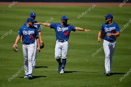 Los Angeles Dodgers first baseman Matt Beaty, second from right, gestures to teammates Luke Raley, left, Zack McKinstry, second from left, and DJ Peters during the restart of spring training, in Los Angeles