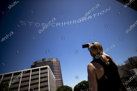 Artist and activist Bamby Salcedo takes pictures with her phone as five planes fly over and skytype her words 'Stop Crimmigration Now' over landmarks in downtown Los Angeles, California, USA, 03 July 2020. In Plain Sight is a coalition of 80 artists united to create an artwork dedicated to the abolition of immigrant detention.