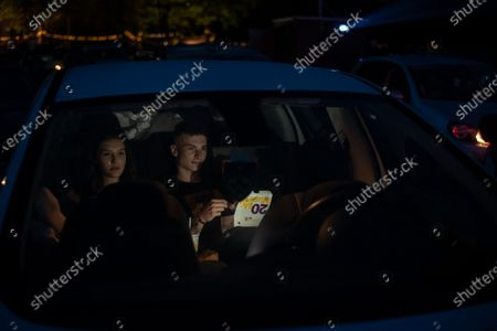 """A young couple in the back of their car eat fast food while watching a movie """"Grease"""" with John Travolta and Olivia Newton-John at a temporary drive-in cinema parking lot. Due to the spread of the coronavirus (COVID-19) the City Cinema organised outdoor screening."""