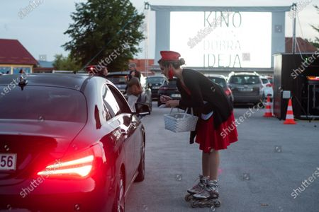 """Stock Image of A waitress takes an order before the screening of a movie """"Grease"""" with John Travolta and Olivia Newton-John at a temporary drive-in cinema parking lot. Due to the spread of the coronavirus (COVID-19) the City Cinema organised outdoor screening."""