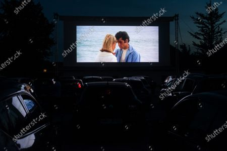 """Stock Photo of People in their cars watch a movie """"Grease"""" with John Travolta and Olivia Newton-John at a temporary drive-in cinema parking lot. Due to the spread of the coronavirus (COVID-19) the City Cinema organised outdoor screening."""