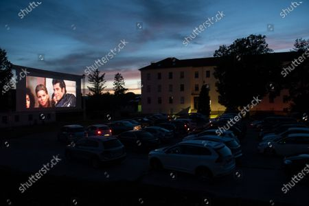 """People in their cars watch a movie """"Grease"""" with John Travolta and Olivia Newton-John at a temporary drive-in cinema parking lot. Due to the spread of the coronavirus (COVID-19) the City Cinema organised outdoor screening."""