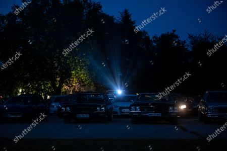 """Stock Picture of People in their cars watch a movie """"Grease"""" with John Travolta and Olivia Newton-John at a temporary drive-in cinema parking lot. Due to the spread of the coronavirus (COVID-19) the City Cinema organised outdoor screening."""