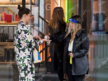 A customer is asked to use hand sanitiser before being allowed to enter George Northwood hair salon in Soho, as barbers and hairdressers are allowed to open for the first time since lockdown.