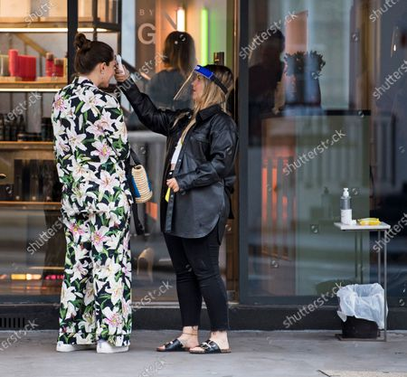 A customer has her temperature taken before being allowed to enter George Northwood hair salon in Soho, as barbers and hairdressers are allowed to open for the first time since lockdown.
