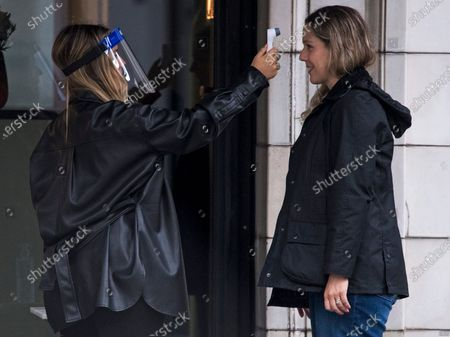 Stock Image of A customer has her temperature taken before being allowed to enter George Northwood hair salon in Soho, as barbers and hairdressers are allowed to open for the first time since lockdown.