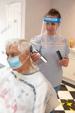 A hairdresser working with a face shield on. Mr Snips hair studio and Barber shop in Petts Wood high street, Petts Wood, South East London, has reopened today after three months of coronavirus lockdown. Staff and customers have to wear PPE.