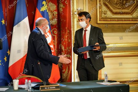Green Party Europe-Ecologie-Les Verts (EELV) Gregory Doucet, right, receives the mayor scarf from the Lyon's outgoing mayor Gerard Collomb, left, during the Lyon council meeting, in Lyon, central France, . The Lyon council meeting elected Gregory Doucet officially after he won the Lyon 2020 mayoral elections last weekend
