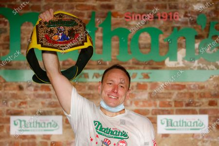 Competitive eater Joey Chestnut celebrates after setting a new world record with 75 hot dogs to win the men's division of the Nathan's Famous July Fourth hot dog eating contest, in the Brooklyn borough of New York