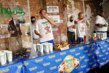 Competitive eater Joey Chestnut, center left, sets a new world record with 75 hot dogs to win the men's division of the Nathan's Famous July Fourth hot dog eating contest, in the Brooklyn borough of New York