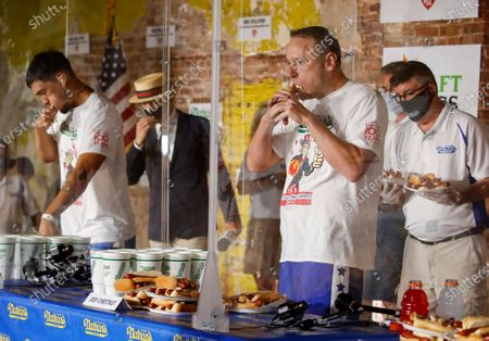 Competitive eater Joey Chestnut sets a new world record with 75 hot dogs to win the men's division of the Nathan's Famous July Fourth hot dog eating contest, in the Brooklyn borough of New York. AP Photo/John Minchillo