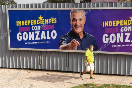 A man with a face mask walks near a billboard for the presidential candidate Gonzalo Castillo, in Santo Domingo, Dominican Republic, 04 July 2020. Dominicans go to the polls on 05 July to choose the successor to President Danilo Medina, in office since 2012, amid the current coronavirus pandemic, whose cases have increased in recent weeks, which could increase abstention.