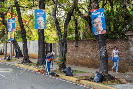 People with masks are seen as they walk next to posters of the presidential candidate Luis Abinader, in Santo Domingo, Dominican Republic, 04 July 2020. Dominicans go to the polls on 05 July to choose the successor to President Danilo Medina, in office since 2012, amid the current coronavirus pandemic, whose cases have increased in recent weeks, which could increase abstention.